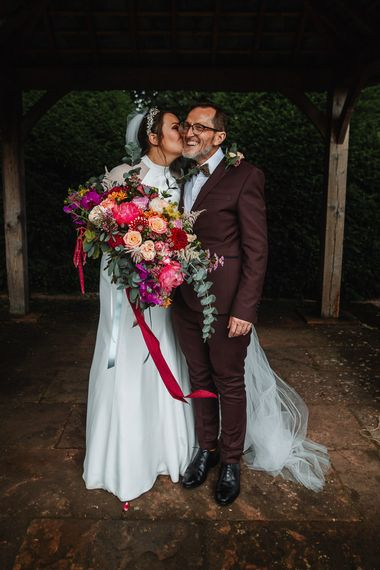 Bride and Father of the Bride in Burgundy Suit with Bride Holding a Pink Wedding Bouquet