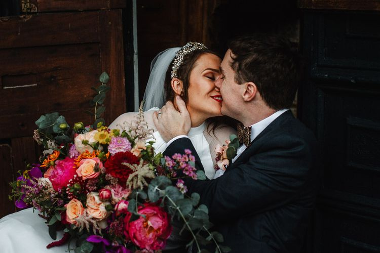 Groom Kissing His Bride Whilst Holding a Pink Wedding bouquet