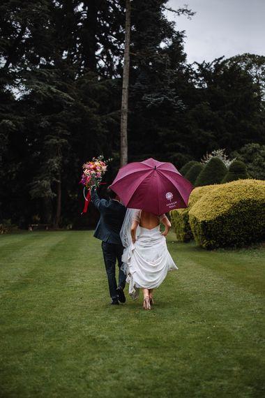 Bride and Groom Walking Under an Umbrella at their Askham Hall Wedding
