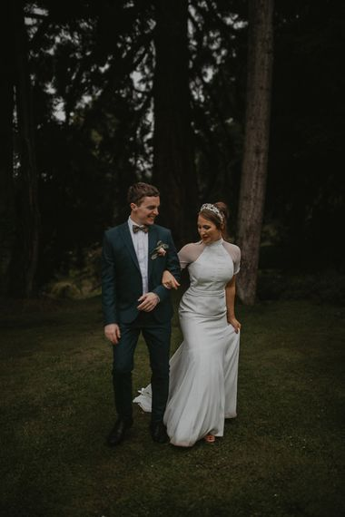 Bride in Bespoke Wedding Dress with Cap Sleeves and Bridal Crown and Groom in Navy Suit and Bow Tie