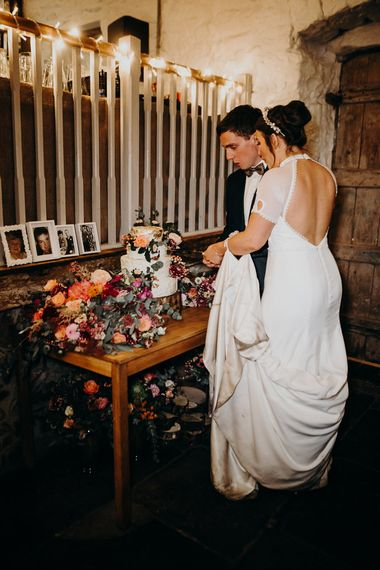 Bride and Groom Cutting the Cake at Their Askham Hall Wedding