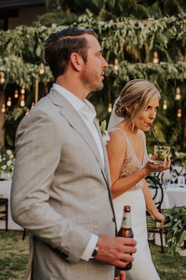 Bride and groom have a drink to celebrate their wedding