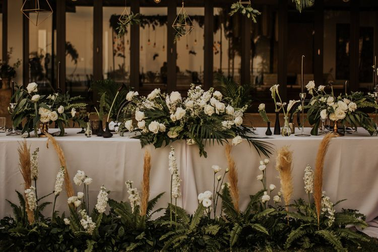 Wedding table decor with white flowers, foliage and pampas grass