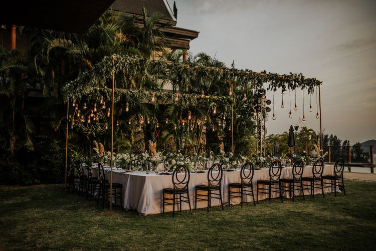 Stunning intimate wedding set up with hanging light installation and foliage