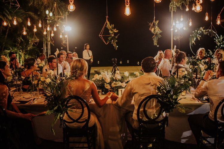 Bride and groom at intimate destination  wedding with hanging lights and geometric decor