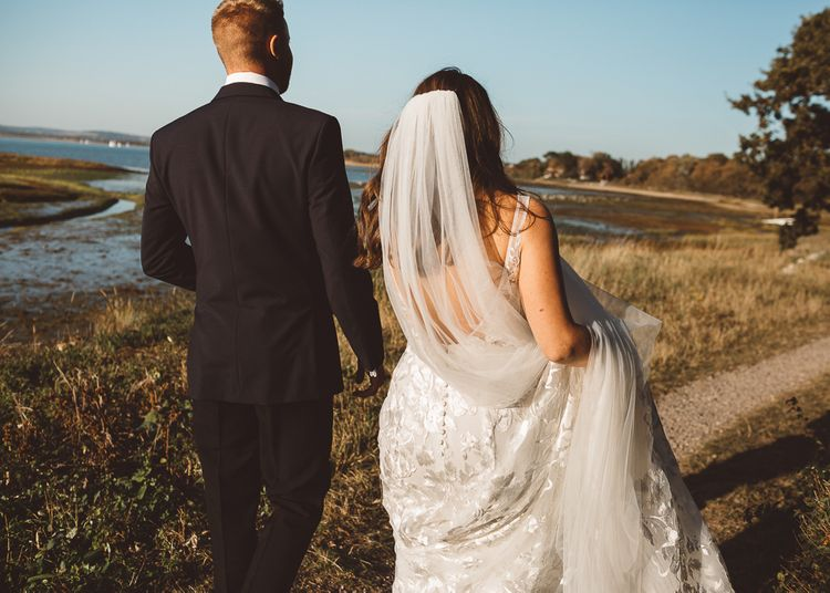 Back of brides Made With Love Bridal dress and veil at romantic outdoor wedding