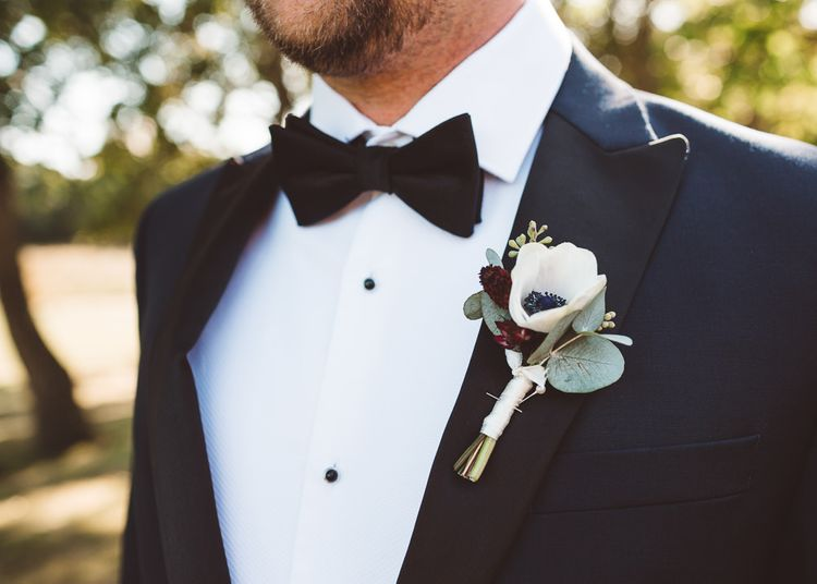 Groom wearing floral buttonhole and bow tie at Crouchers Orchards for outdoor wedding ceremony