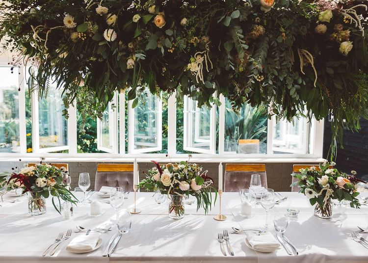 Hanging foliage and floral table arrangements styled with gold candlesticks for intimate and romantic wedding