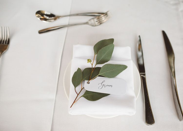 Place settings for intimate wedding styled with eucalyptus