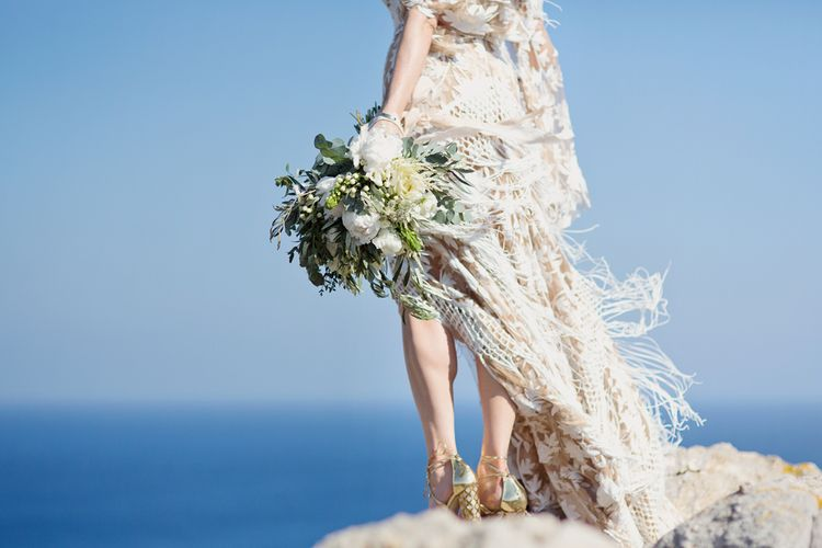 Bride in Rue De Seine Dakota Wedding Dress with Fringe Detail Holding a White and Green Bouquet on a Cliff