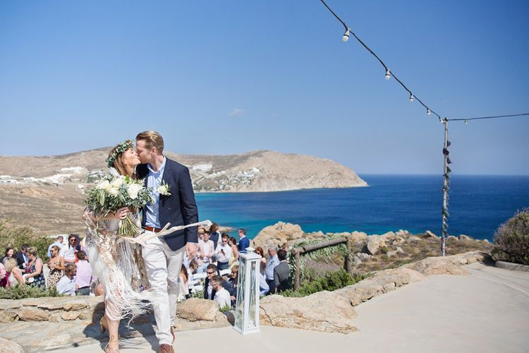 Bride in Rue De Seine Dakota Wedding Dress with Fringe and Groom in Chino's and Navy Blazer Kissing