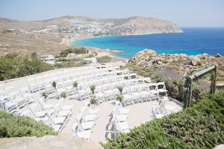 Cliff Top Wedding Ceremony Set Up with White Chairs and Views of Mykonos