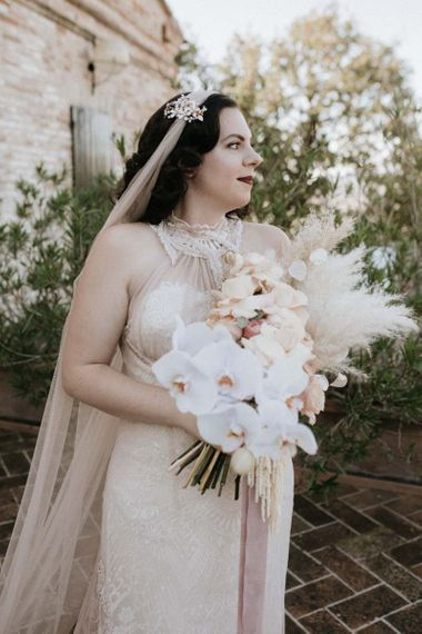 Bride in homemade wedding dress holds  beautiful orchid bouquet with pampas grass