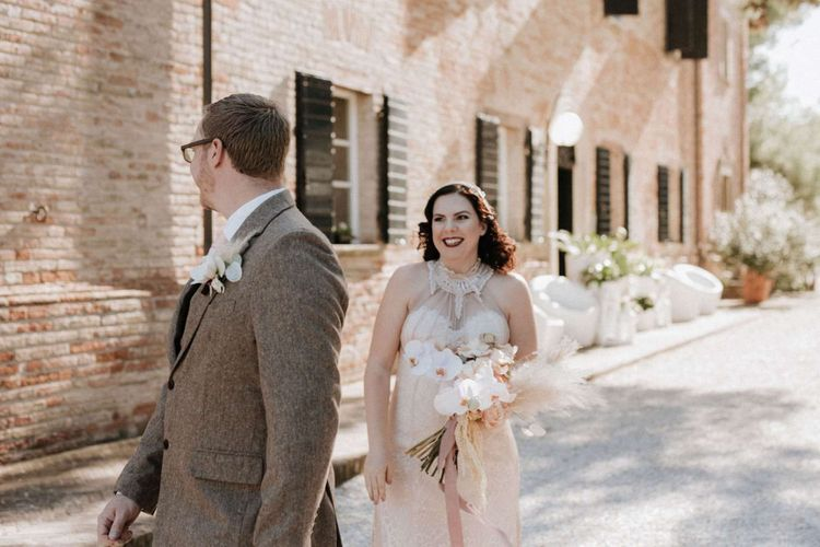 Groom turns to see bride holding orchid bouquet at first look