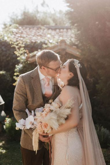 Bride holding orchid bouquet kisses groom at Italian wedding