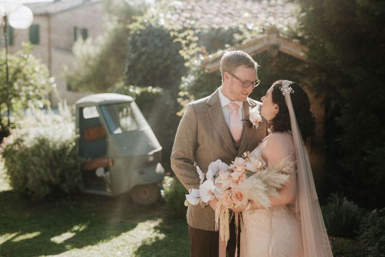 Bride holding orchid bouquet with groom at Italian wedding venue