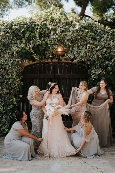Bridesmaids tend to the bride who holds an orchid bouquet