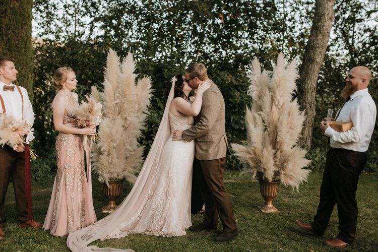 Bride and groom kiss at outdoor ceremony with pampas grass decor