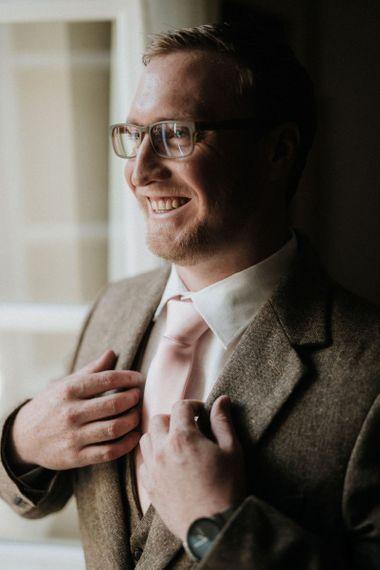 Groom preparations with tweed suit and pink tie