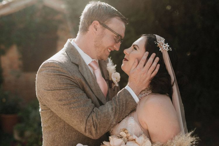 Bride holds orchid bouquet as she looks at groom