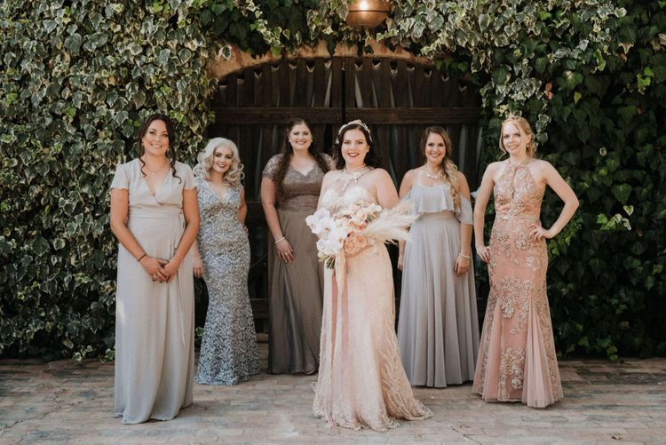 Mismatched bridesmaid dresses with bride in homemade wedding dress holding orchid bouquet