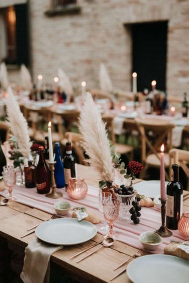 Gorgeous wedding table decor with pampas grass, blush candles and pink glassware