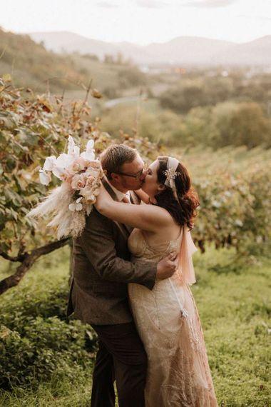 Bride holding orchid bouquet kisses groom