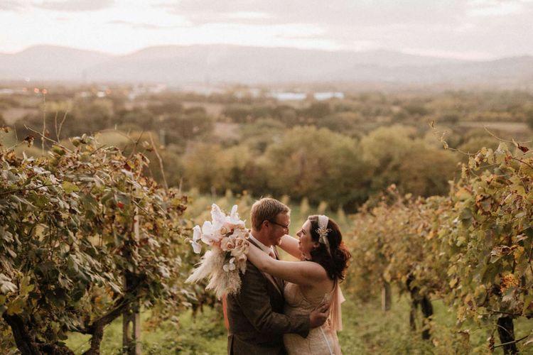 Groom in tweed wedding suit kisses