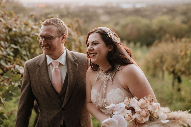 Bride holding orchid bouquet with groom at destination wedding in Italy