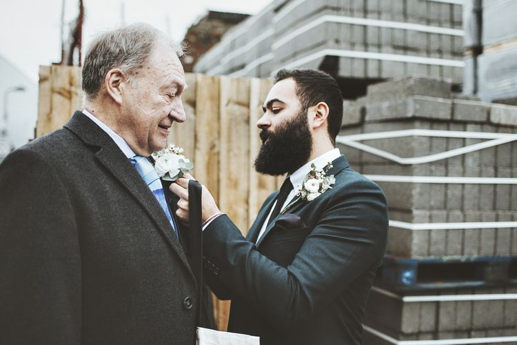 Groom Pinning Buttonhole on Father of the Bride