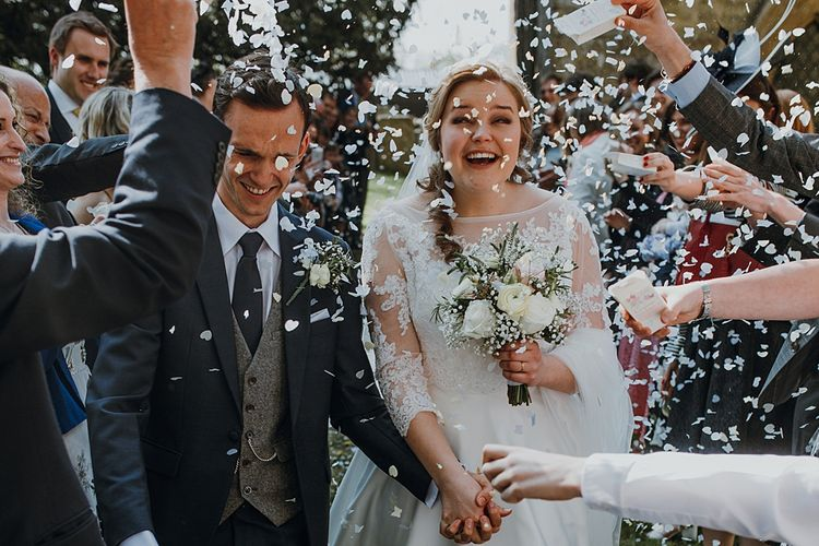 Confetti Exit | Bride in Bespoke Gown | Groom in Navy Suit | Homemade, Homegrown Village Marquee Wedding with Greenery | Rustic DIY Decor | Claire Fleck Photography | Second Shooter Oscar Davies Photography