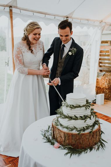 Cutting the Cake | Bride in Bespoke Gown | Groom in Navy Suit | Homemade, Homegrown Village Marquee Wedding with Greenery | Rustic DIY Decor | Claire Fleck Photography | Second Shooter Oscar Davies Photography