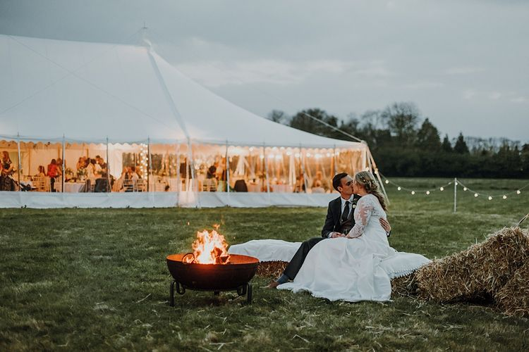 Fire Pit | Bride in Bespoke Gown | Groom in Navy Suit | Homemade, Homegrown Village Marquee Wedding with Greenery | Rustic DIY Decor | Claire Fleck Photography | Second Shooter Oscar Davies Photography
