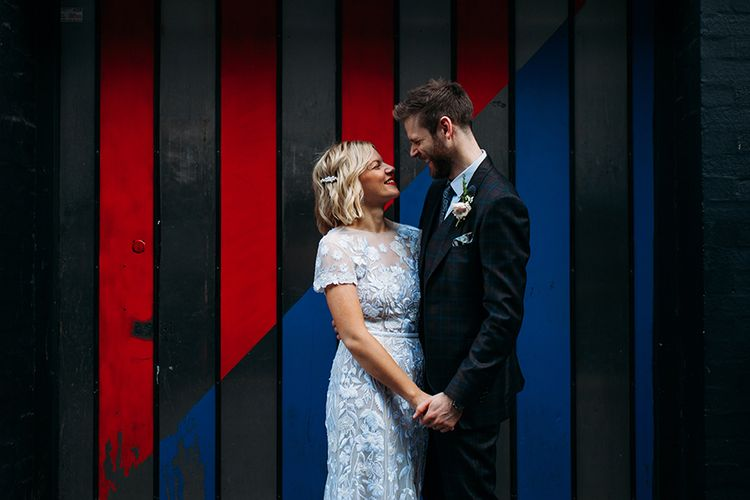 Bride in Lace Hermione De Paula Wedding Dress and Groom in Ted Baker Suit  Embracing