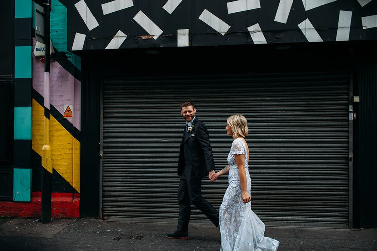Stylish Bride in Lace Hermione De Paula Wedding Dress and Groom in Ted Baker Suit Walking Through East London