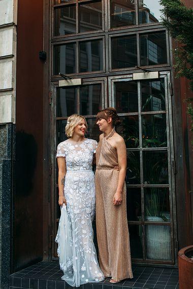 Bride in Lace Hermione De Paula Wedding Dress and Bridesmaid in Metallic The Jestset Diaries Avalon Jumpsuit  via ASOS
