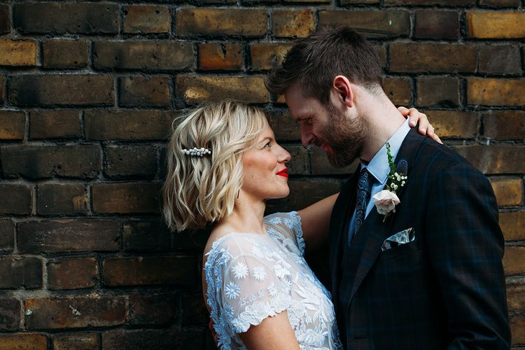 Bride in Lace Hermione De Paula Wedding Dress with Bob Hair & Pearl Slide  and Groom in Ted Baker Embracing