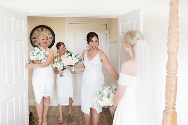 Bridesmaids in white dresses first look