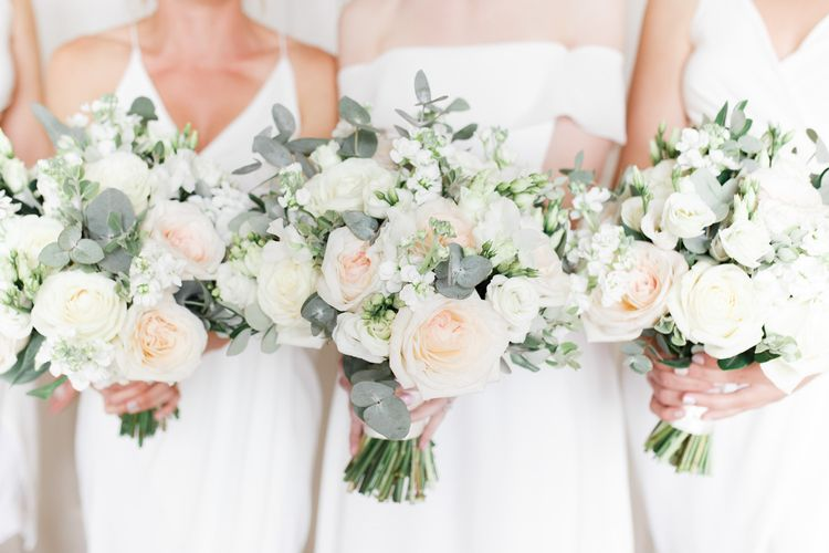 White and green bridal bouquets with roses, stocks and eucalyptus
