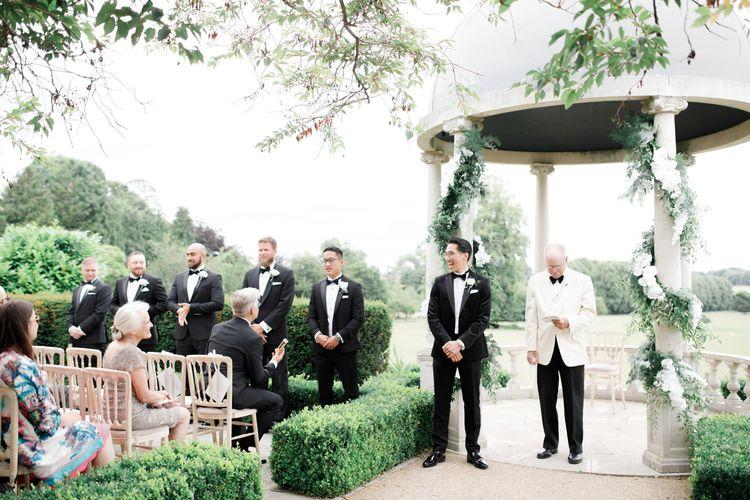 Groomsmen in black tie suits at outdoor ceremony