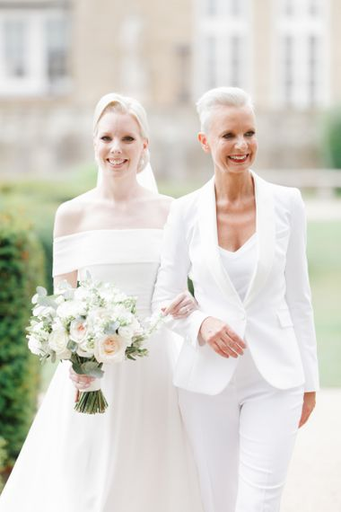 Mother of the bride in white suit and bride in Mori Lee off the shoulder wedding dress