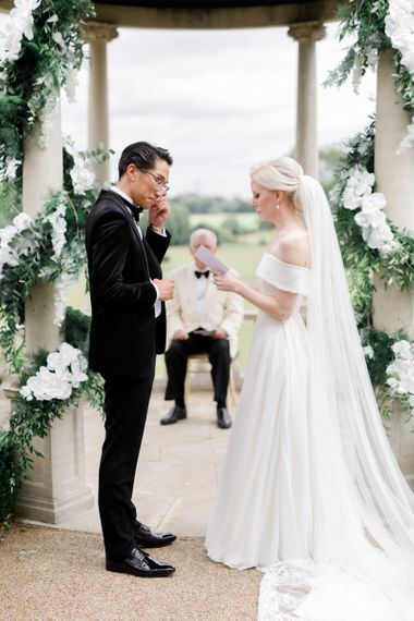 Bride in off the shoulder wedding dress and groom in tuxedo exchanging vows