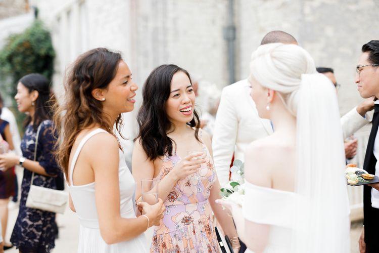 Bride in off the shoulder wedding dress talking to wedding guests