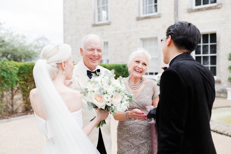 Bride and groom talking to family