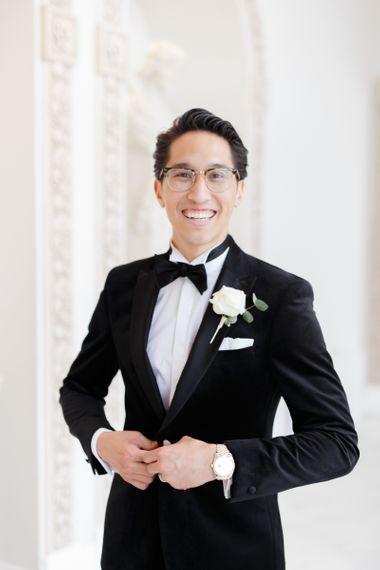 Groom in black tie suit and bow tie