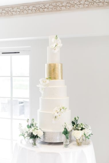 Tall wedding cake with different size layers and gold leaf detail
