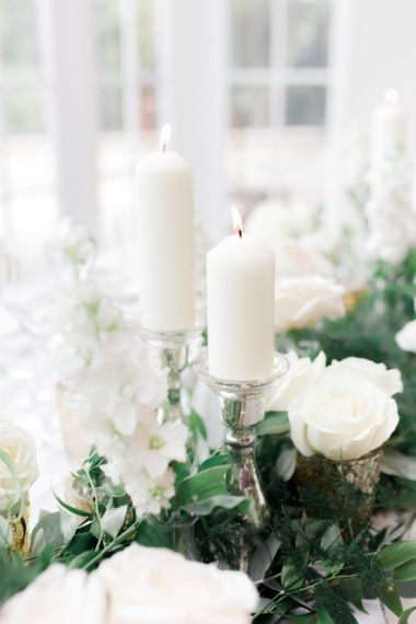 White candles on silver candle holders