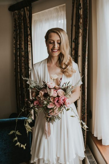 Bride in Houghton NYC Tiered Wedding Dress with Blush Pink and Raspberry Bridal Bouquet