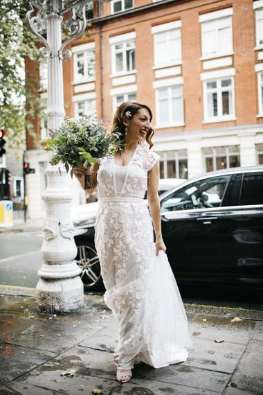 Bride wearing Phase Eight Wedding Dress teamed with hair accessory and white foliage bouquet