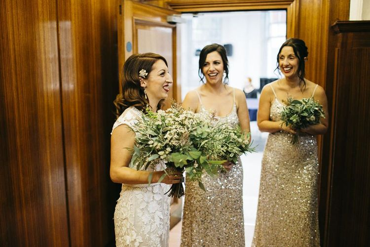 Bride wearing Phase Eight Wedding Dress and her bridesmaids wearing embellished dresses teamed with white foliage bouquets